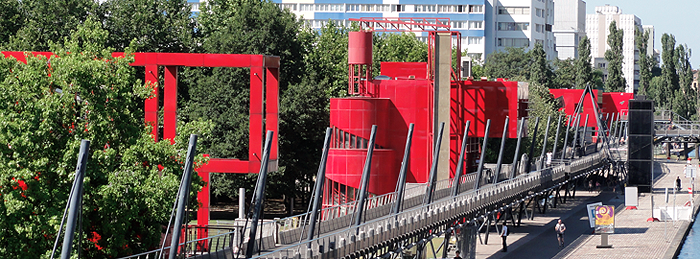 Red steel buildings, trees, pedestrian bridge