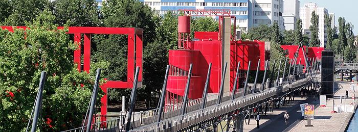 Red steel buildings, trees, pedestrian bridge