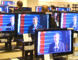TVs in department store showing Obama