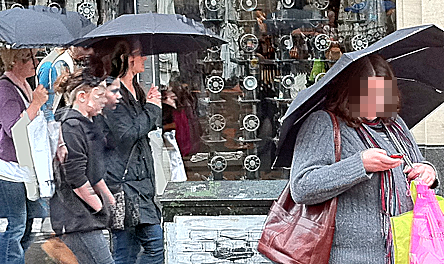 People with umbrellas in the street. Face of phone user pixelated out.