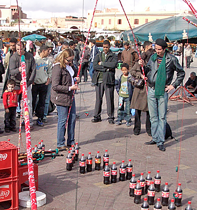 People playing a game with Coke bottles and fishing rod