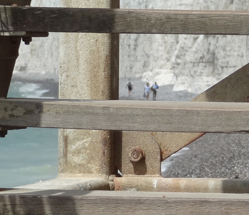 People seen through wooden steps at a beach