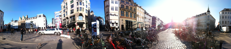 Parked bicycles, blue sky, buildings, shadow of the photographer