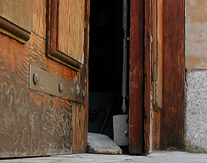 A wooden wedge in an old door used side on to wedge open a door