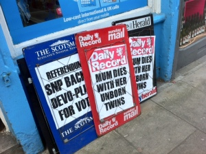 """three signs stacked against a blue shopfront. The posters say """"Referendum: SNP backs devo-plus for vote""""; and """"Mum dies with her unborn twins."""""""