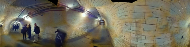 Panoramic image of a white-tiled tunnel.