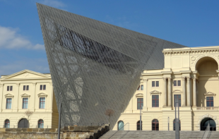 Classical, cream coloured 2-storey facade intersected by 4-storey metalic, meshed pyramid shape.