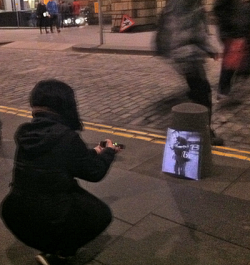 Guide kneeling while projecting image onto a bollard in the street, Edinburgh Old Town.
