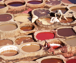 brown and red dye-filled 1.2 m circular pits with young man wading and treating leather