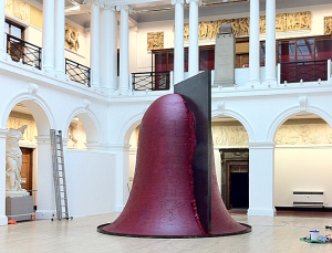 5 metre high red, bell-shaped sculpture with black wedge