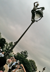 Man balancing soccer ball on his head while poised on an old fashioned lamp post. People photographing from below.