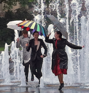 Three well-dressed women with umbrellas dancing under fountain's water jets