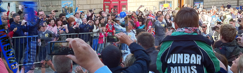 Crowd of people lining the street with cameras. the torch bearer is barely visible.