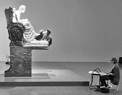 Brooding sculpture of whole body in profile being sketched by an artist on a chair