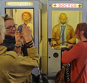 Lifesize manequins in glass boxes labelled chiropodist and doctor. People looking and taking photographs.