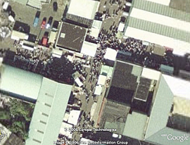 Google maps aerial view of busy crossroads in the market, showing buildings and people.