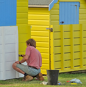 Man painting beach huts bright yellow