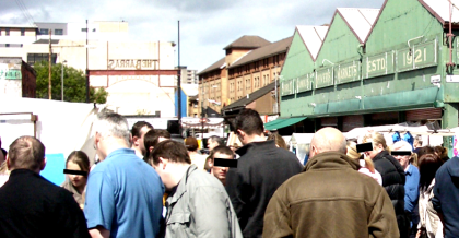 Crowd in an open air market. Faces are occluded.
