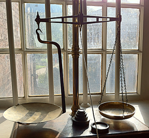 Old fashion balance scales in front of a Victorian window
