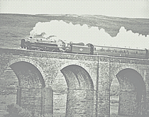 Steam train on a viaduct passing through the countryside
