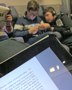Two boys playing on a smartphone; iPad in foreground with page from The Routledge Handbook of Emotions and Mass Media