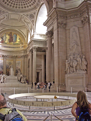 Interior of a large, classical cathedral-like building, with pendulum, its weighted orb at the bottom, and angle markings on a 30 cm high fence defining the sweep of the pendulum. There are some tourists looking at it.