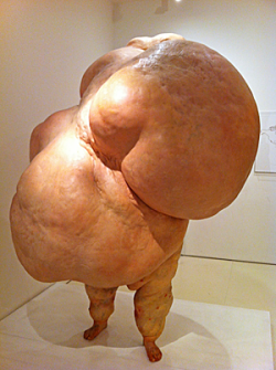 Life-sized sculpture that looks like a grotesque naked human body on legs, but without head or arms. Just a lump of fat really.