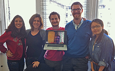 5 people standing in front of a window and looking at the camera. A 6th person appears via video link as a face on a laptop being held by one of the group.