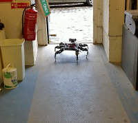 Spidery robot about to exit through a door in a workshop