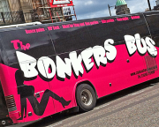 Black and red bus with the name on the side and silhouette of female