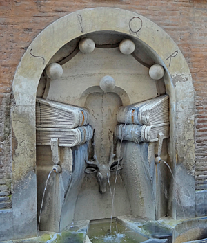 Like an archway or niche set into a wall, depicting books with water coming out of them. There's a stags head in the middle of the niche. It's all of marble set into a brick wall, and it's a bit weathered.