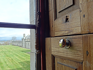 View through window showing wooden shutter, lawn, distant hills, wing of stately home