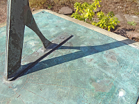 Close up of green tinted metal sundial