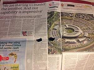 Shows headline 'We are starting to master the internet. And our capability is impressive.' shows picture of GCHQ from the air. Paper is crumpled and there are eye holes cut into it.