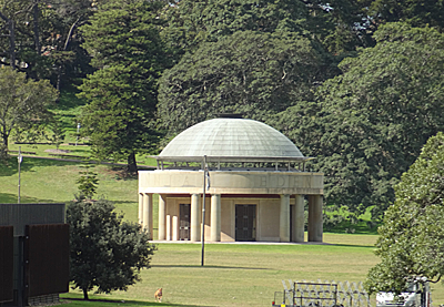 A neo-classical, but modern, domed folly set in parkland with trees
