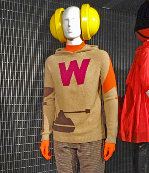Life-size male mannequin wearing large, yellow plastic headphones and a brown jumper with W and a tank on it