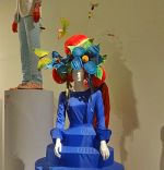 Life-size female mannequin wearing a blue ziggurat dress and floral headgear