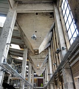 Grey four-storey concrete interior with coal hoppers projecting from ceiling