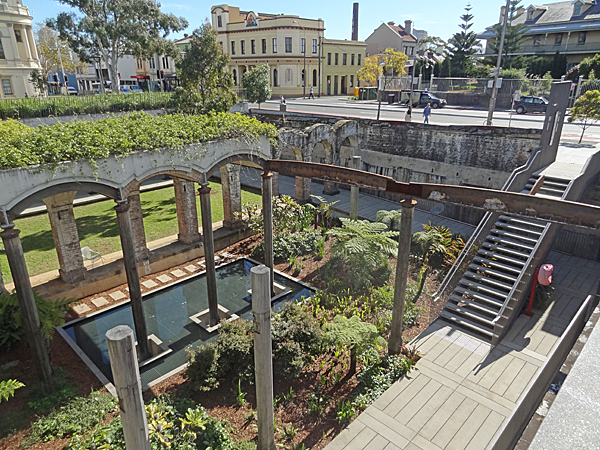A modern conversion of the sunken reservoir into a formal park. There are steps leading down from the street, which is visible and lined with Victorian buildings.
