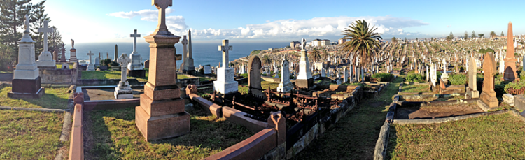 Dramatic view over gravestones to the ocean beyond; blue sky