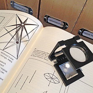 "Open book with abstract drawings, box files marked ""hermeneutics"" in the background, magnifying glass with CIBA brand mark. Pho is in square format."