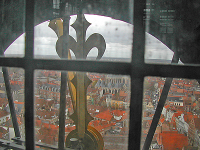 Looking through window behind clock face across Medieval city