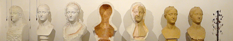Seven casts of a woman's head, arranged in a row and in various stages of completion
