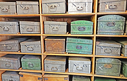 Old style metal boxes on wooden shelves