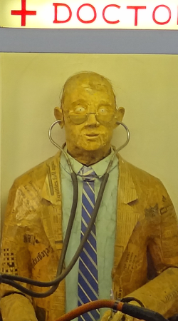 Life size papier mache doctor with stethoscope in a booth at an amusement pier