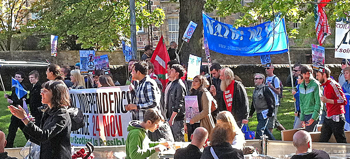 Banner waving demonstrators near a park with people sitting outside a coffee shop in the foreground
