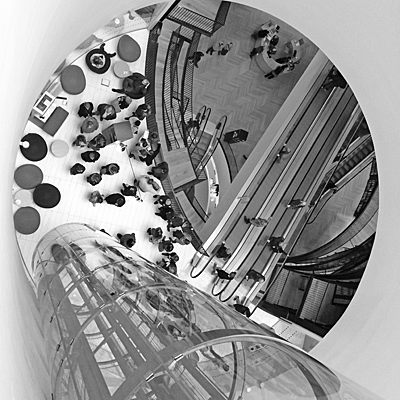 Framed by circular shape of the atrium; shows glass tube of lift shaft; people and escalators below; black and white picture in square format