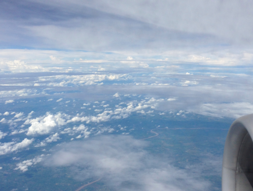 View from aircraft window; river below, clouds, part of engine showing