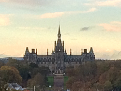 Neo-gothic fantasy building with spires and finials, a bit like Hogwarts; elevation view at dusk