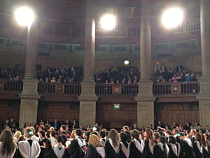Big classical hall, high columns, gallery, graduates in gowns with backs to camera, bright ceiling lights